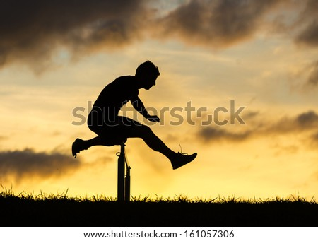 silhouette of an athlete in hurdling in track and field - stock photo