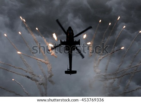 Silhouette of an attack helicopter firing flares, storm is coming - stock photo