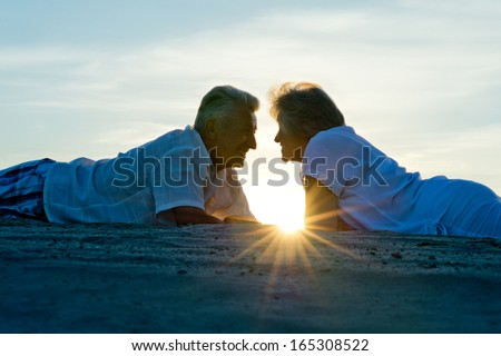 Silhouette of an elderly couple in love at sunset - stock photo