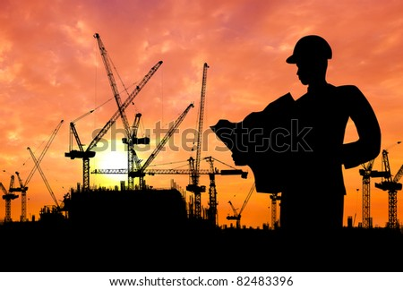 silhouette of an engineer working on construction site at sunset - stock photo