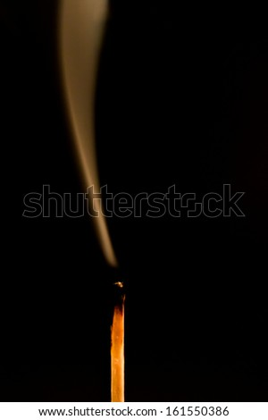 Silhouette of an extinguished match flame isolated on black background