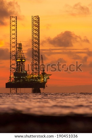Silhouette of an offshore drilling rig and an orange sunset - stock photo