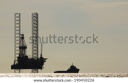 Silhouette of an offshore drilling rig and supply vessel  - stock photo