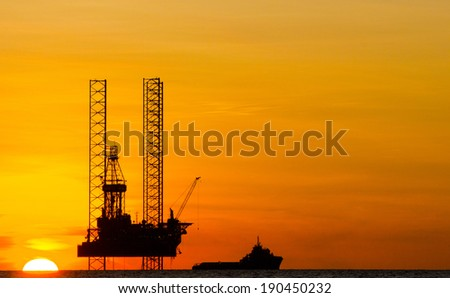 Silhouette of an offshore drilling rig and supply vessel at an orange sunset - stock photo