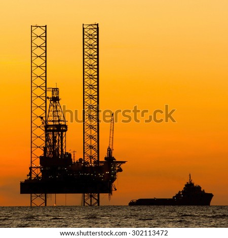Silhouette of an offshore drilling rig and supply vessel at sunset - stock photo