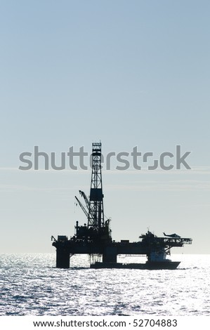 silhouette of an oil drilling rig, in offshore area, with a supply vessel along side and helicopter landed - stock photo