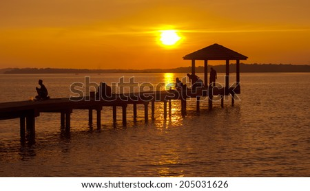 Silhouette of an old jetty with people doing early sport