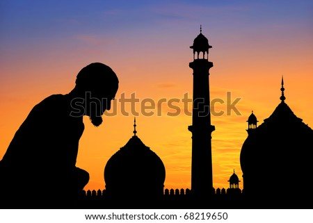 Silhouette of an old muslim praying at sunset, Great Mosque, Delhi, India.