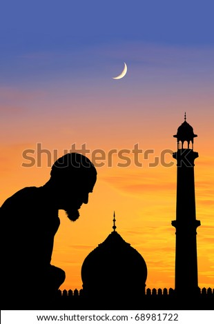 Silhouette of an old muslim praying at sunset, Great Mosque, Delhi, India. - stock photo