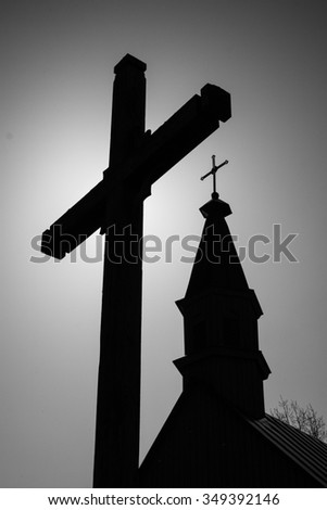 Silhouette of an old wooden catholic chapel and big cross in western Lithuania