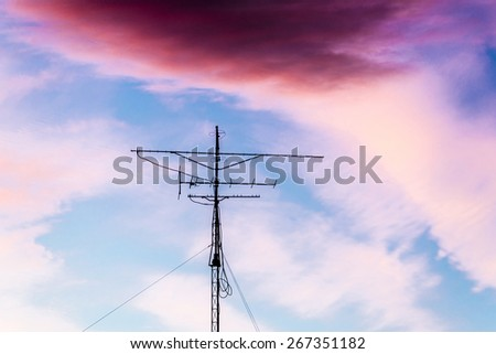 Silhouette of antenna backlit at sunset with colorful sky clouds - stock photo