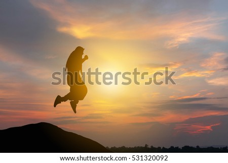 Silhouette of Arab Middle Eastern Business man Celebration Success Happiness Sunset Evening Sky Background