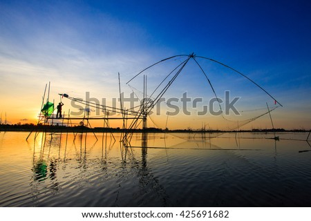 Silhouette of asian fisherman in action casting a big net for catching freshwater fish in nature river in the early morning before sunrise - stock photo