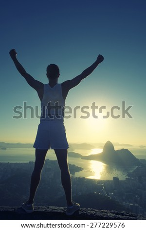 Silhouette of athlete in white sport uniform standing with champion arms raised in front of Rio de Janeiro Brazil sunrise skyline overlook at Sugarloaf Mountain - stock photo