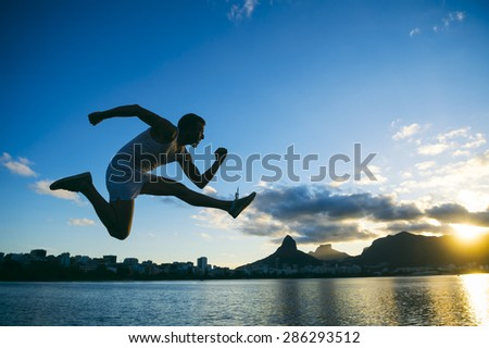Silhouette of athlete jumping in front of the sunset skyline at Lagoa lagoon in Rio de Janeiro, Brazil  - stock photo