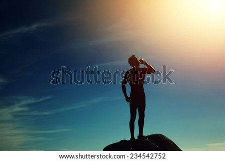 Silhouette of athlete refreshing with bottle of water after run, muscular build beautiful man drinking water after fitness outdoors,sporty fit man drinking water at sunny day standing on mountain hill - stock photo