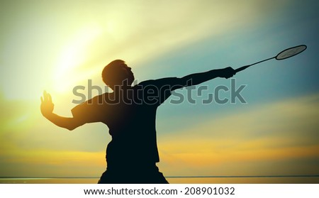 Silhouette of Badminton Player against Evening Sky - stock photo