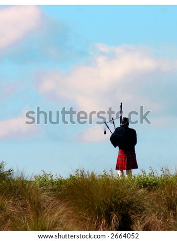 silhouette of bagpiper playing on a hill walking away - stock photo