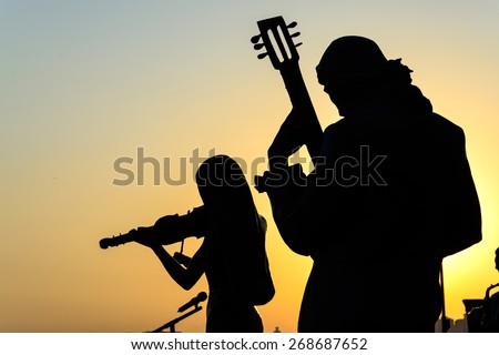 Silhouette of band playing the music at sunrise - stock photo
