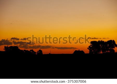 Silhouette of barn and trees on farm in South Dakota - stock photo