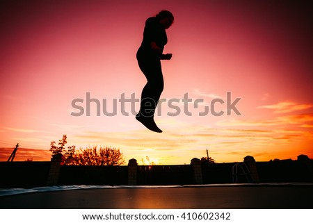 Silhouette Of Beautiful Plus Size Young Woman Girl Jumping On Trampoline On Evening Red, Pink Colorful Sunset Sky Background - stock photo