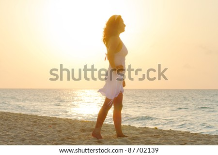 Silhouette of beautiful woman on the beach at sunrise