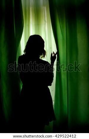 silhouette of beautiful woman standing at green curtains and looking at window - stock photo