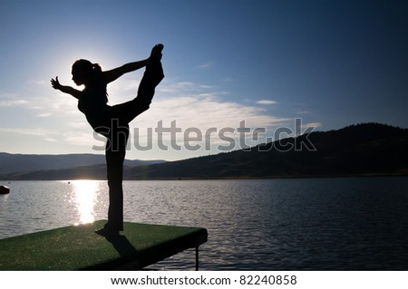 Silhouette of beautiful young girl doing a dancers pose by a lake - stock photo