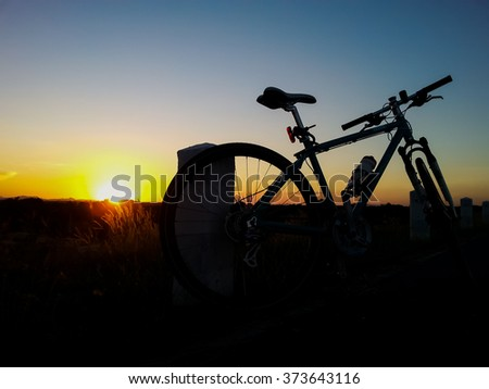 Silhouette of  bicycle against sunset