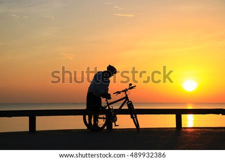 Silhouette of bicycle on the beach in the morning with vibrant sky background