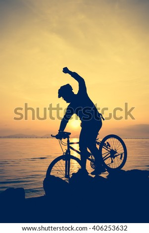Silhouette of bicyclist riding the bike on rocky trail at seaside, on colorful sunset sky background. Active outdoors lifestyle for healthy concept. Action of winner or successful people. Vintage. - stock photo