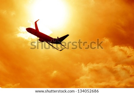 Silhouette of big airplane on beautiful orange sunset background, fast aerial transport, traveling and voyage concept - stock photo