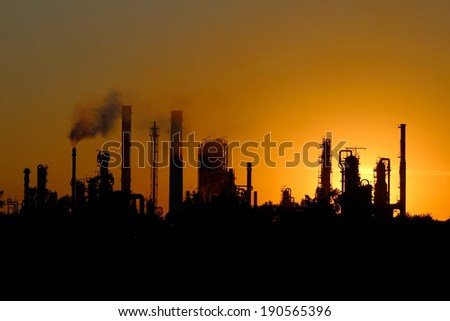 silhouette of big oil refinery factory  during sunset - stock photo