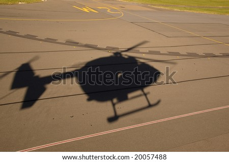 Silhouette of BK117 / EC145 helicopter taking off or landing at airport - stock photo