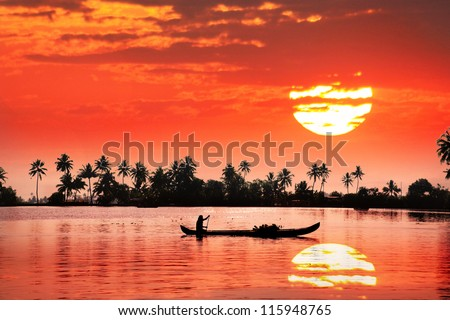 Silhouette of boat and fisherman in backwaters at palms and big orange sun background
