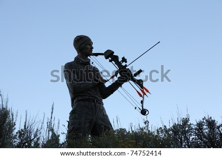silhouette of bow hunter holding bow and arrow at dusk