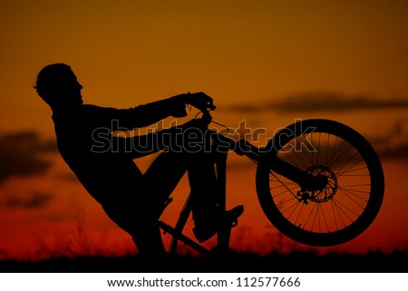 silhouette of boy cyclist in motion on the background of beautiful sunset (dawn) - stock photo