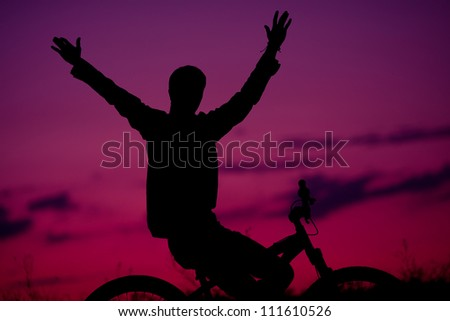 silhouette of boy cyclist in motion on the background of beautiful sunset (dawn) with hands up