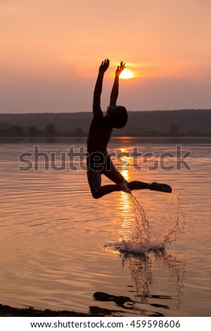 Silhouette of boy jumping into water on sunset