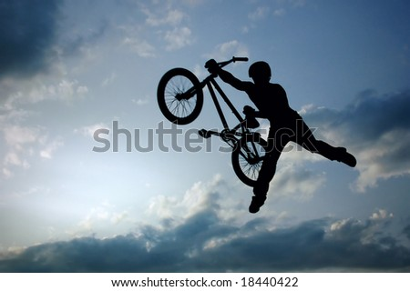 silhouette of boy with bicycle jumping in air