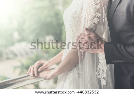 Silhouette of bride and groom are holding a bouquet of white flowers near the window. vintage tone color - stock photo