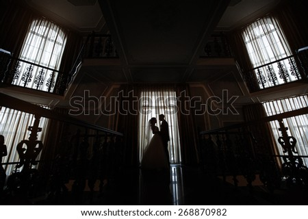 Silhouette of bride and groom in the interior against the window. - stock photo