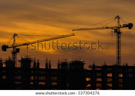 Silhouette of building and construction crane with sunset morning sky