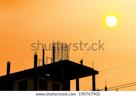 Silhouette of building construction at sunset while some workers are working - stock photo