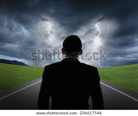 silhouette of business man look rainstorm clouds and lightning with asphalt road and grass, business concept - stock photo