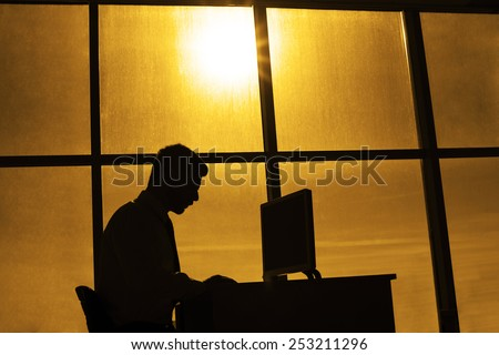 silhouette of business man on  background office room window of beautiful sunset sky with sun shine rays alone Businessman sit and type print text on pc computer monitor screen Idea late hard work - stock photo