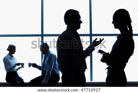 Silhouette of business people chatting in the corridor - stock photo