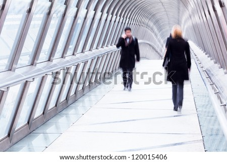 silhouette of business people walking over a pedestrian bridge in Paris, La Defense - stock photo