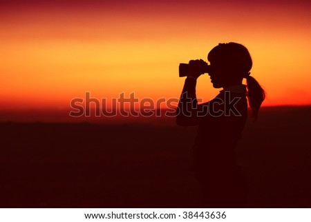 Silhouette of Business Woman with Binoculars Standing on a Hilltop - stock photo
