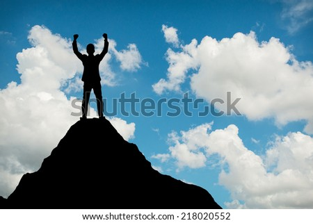 Silhouette of businessman hold up hands on the peak of mountain,success concept